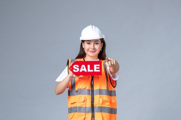 Vooraanzicht van vrouwelijke bouwer met rood verkoopbord op grijze muur
