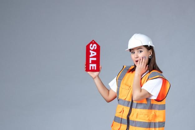 Vooraanzicht van vrouwelijke bouwer met rood verkoopbord op witte muur