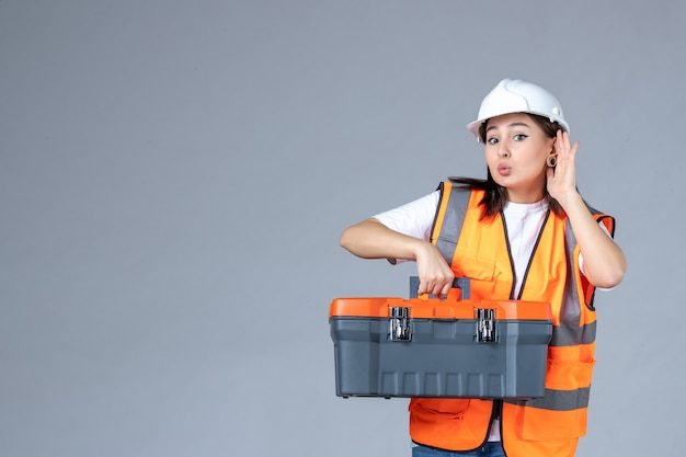 Vooraanzicht van vrouwelijke bouwer met zware gereedschapskoffer op grijze muur