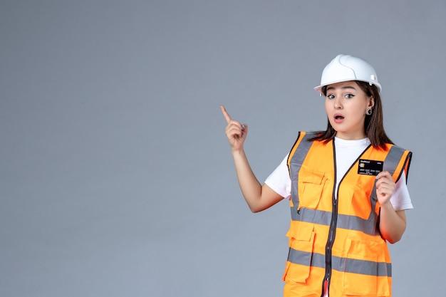 Vooraanzicht van vrouwelijke bouwer met zwarte bankkaart in haar handen op grijze muur