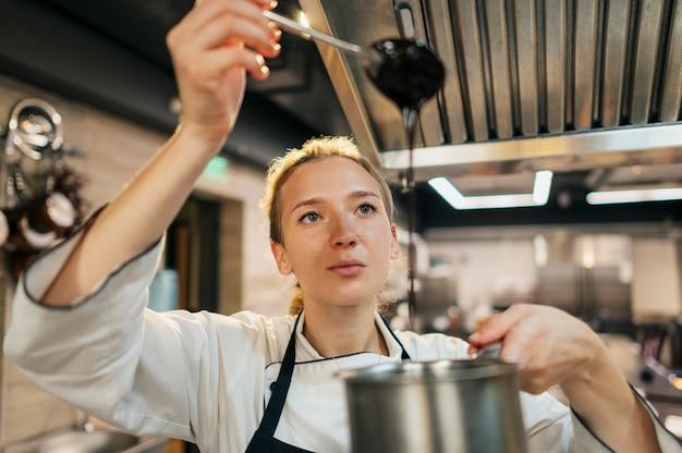 Vooraanzicht van vrouwelijke chef-kok die de dikte van de saus controleert