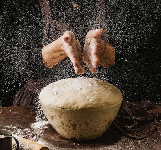 Vooraanzicht van vrouwelijke chef-kok die haar handen met bloem bestrooit alvorens pizzadeeg te behandelen