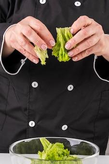 Vooraanzicht van vrouwelijke chef-kok die salade werpt