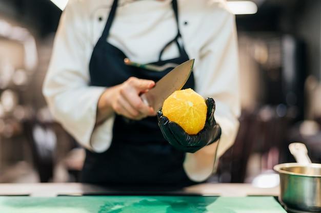 Vooraanzicht van vrouwelijke chef-kok die sinaasappel snijdt