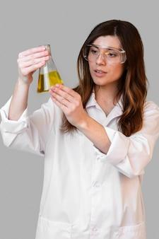 Vooraanzicht van vrouwelijke chemicus die met veiligheidsbril reageerbuis houden