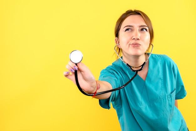 Vooraanzicht van vrouwelijke dierenarts die stethoscoop op gele muur met behulp van