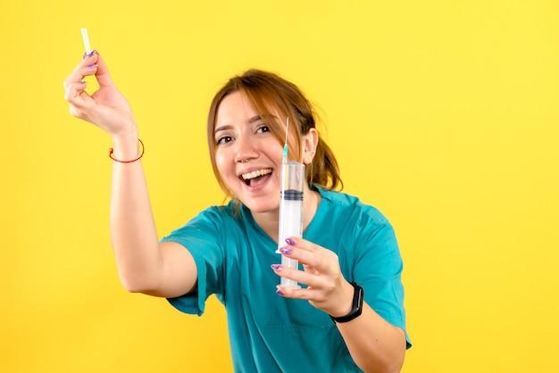 Vooraanzicht van vrouwelijke dierenarts met injectie op gele muur