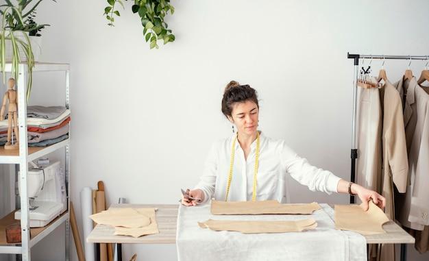 Vooraanzicht van vrouwelijke kleermaker die in de studio werkt