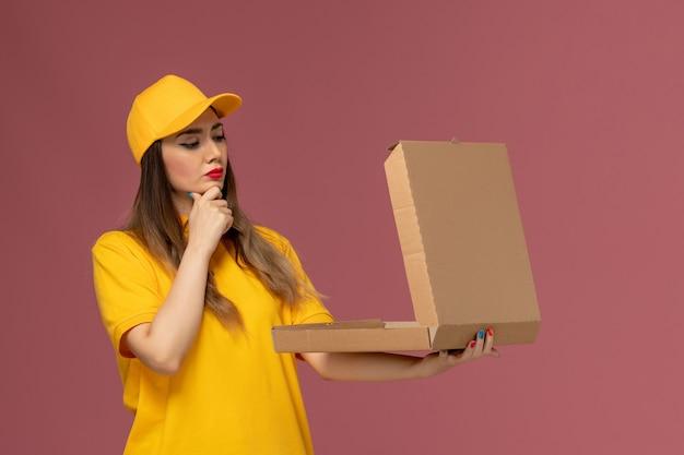 Vooraanzicht van vrouwelijke koerier in geel uniform en pet die open voedseldoos houden die op lichtroze muur denken