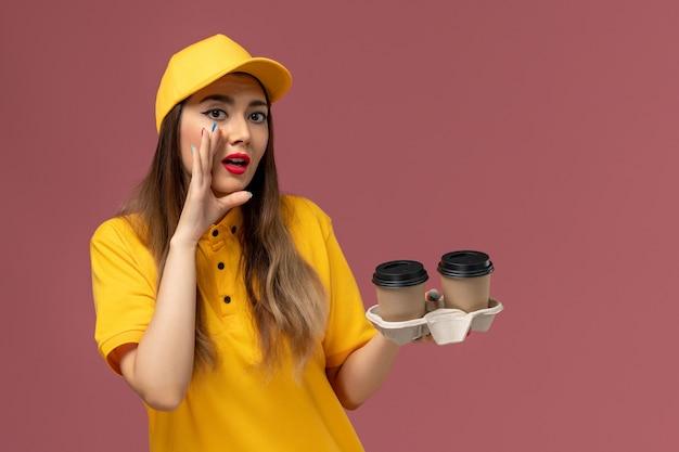 Vooraanzicht van vrouwelijke koerier in geel uniform en pet met koffiekopjes voor bezorging en fluisteren op de roze muur