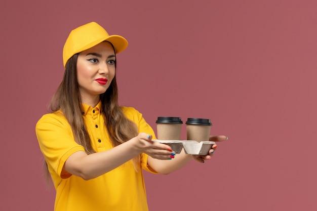 Vooraanzicht van vrouwelijke koerier in geel uniform en pet met koffiekopjes voor levering op de roze muur