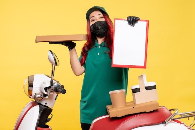 Vooraanzicht van vrouwelijke koerier in masker met bezorgkoffie en voedsel op gele muur