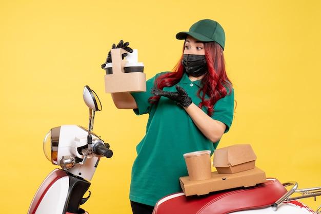 Vooraanzicht van vrouwelijke koerier in masker met bezorgkoffie op gele muur Gratis Foto