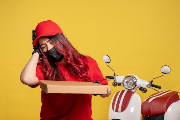 Vooraanzicht van vrouwelijke koerier in masker met de doos van het leveringsvoedsel op gele muur
