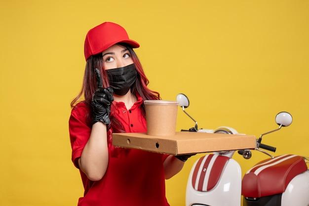 Vooraanzicht van vrouwelijke koerier in masker met leveringsvoedsel op gele muur