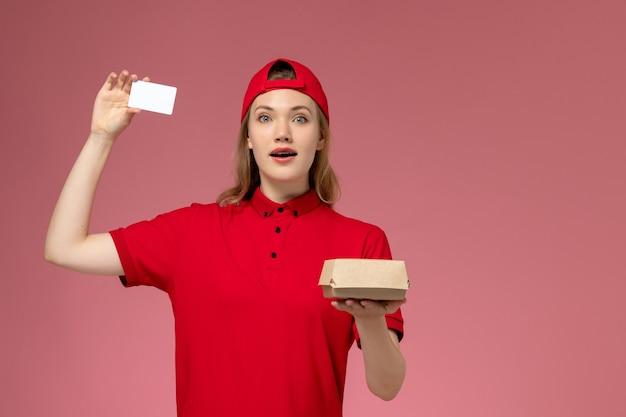 Vooraanzicht van vrouwelijke koerier in rood uniform en cape met klein voedselpakket voor bezorging met witte plastic kaart op de roze muur, service-uniforme bezorgopdracht