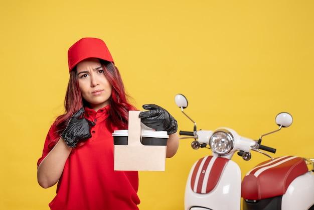 Vooraanzicht van vrouwelijke koerier in rood uniform met koffie op gele muur