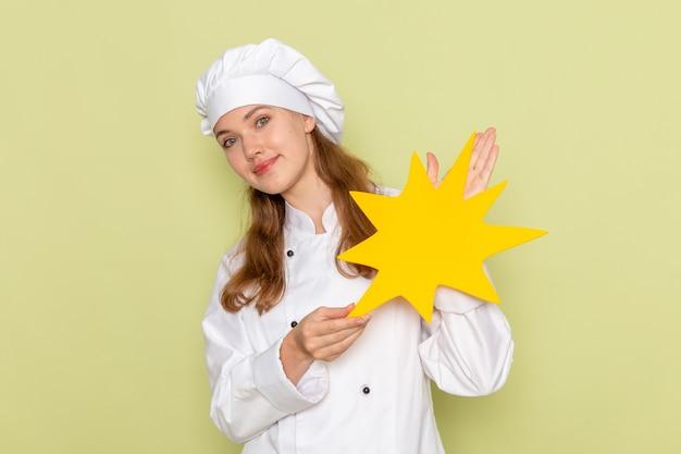 Vooraanzicht van vrouwelijke kok die in wit kokkostuum geel teken met glimlach op groene muur houdt