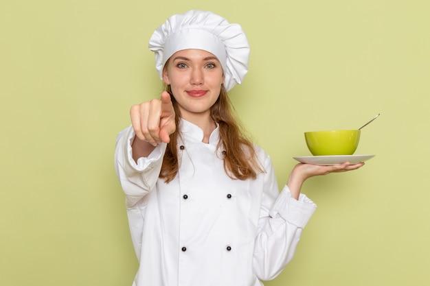 Vooraanzicht van vrouwelijke kok die in wit kokkostuum groene plaat met glimlach op groene muur houden