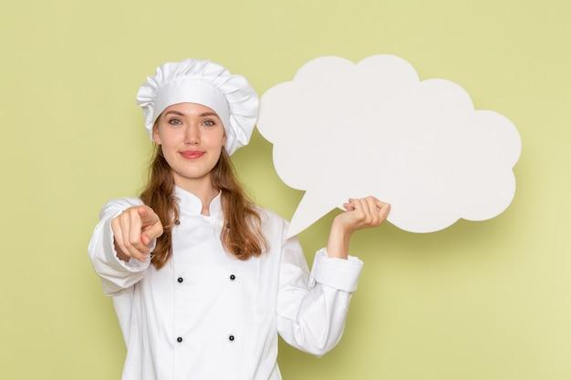 Vooraanzicht van vrouwelijke kok die in wit kokkostuum wit teken met glimlach op groene muur houdt