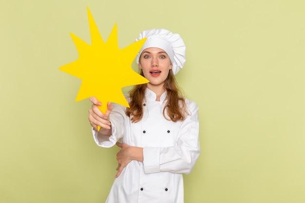 Vooraanzicht van vrouwelijke kok die wit kokkostuum draagt dat een geel teken op de groene muur houdt