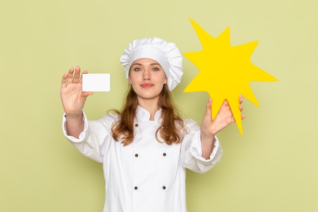 Vooraanzicht van vrouwelijke kok die wit kokkostuum draagt dat geel teken en kaart op groene muur houdt