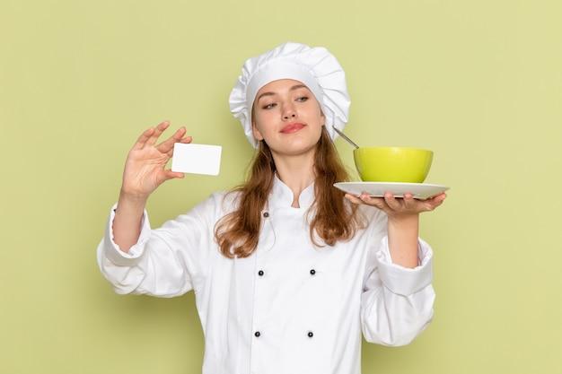 Vooraanzicht van vrouwelijke kok die wit kokkostuum draagt dat groene plaat en kaart op groene muur houdt