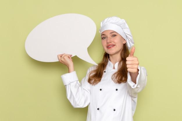 Vooraanzicht van vrouwelijke kok die wit kokkostuum draagt dat groot teken op de groene keuken van de bureaekeuken houdt die vrouwelijke kleur kookt