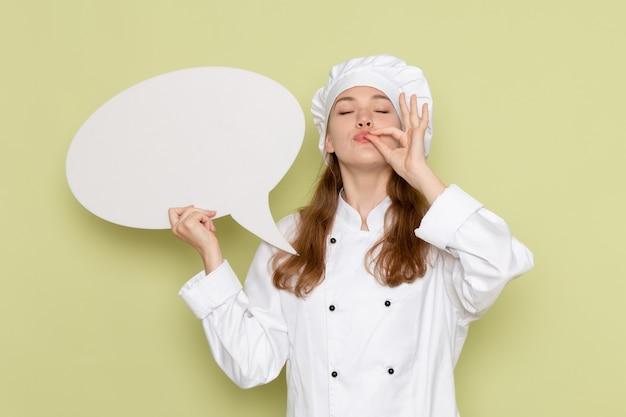Vooraanzicht van vrouwelijke kok die wit kokkostuum draagt dat groot wit teken op de groene muur houdt
