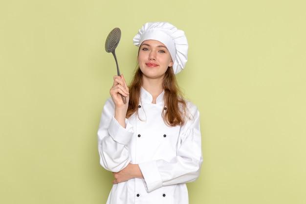 Vooraanzicht van vrouwelijke kok die wit kokkostuum draagt dat grote zilveren lepel met glimlach op groene muur houdt