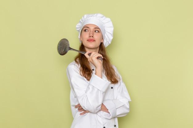 Vooraanzicht van vrouwelijke kok die wit kokkostuum draagt dat grote zilveren lepel op lichtgroene muur houdt
