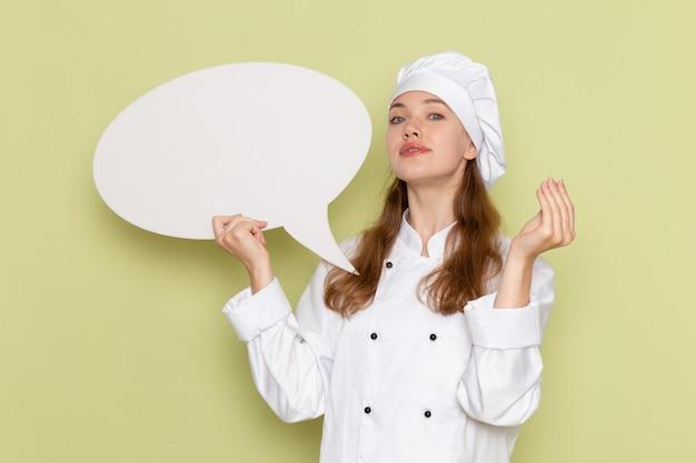 Vooraanzicht van vrouwelijke kok die wit kokkostuum draagt dat wit teken op de groene muur houdt
