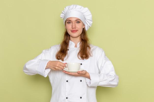 Vooraanzicht van vrouwelijke kok in de witte kop van de kokkostuum op groene muur