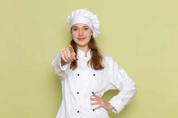Vooraanzicht van vrouwelijke kok in wit kokkostuum dat en op groene muur glimlacht wijst
