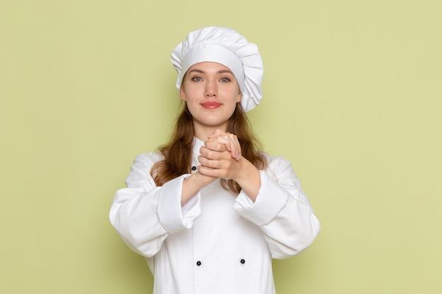 Vooraanzicht van vrouwelijke kok in wit kokkostuum dat en op lichtgroene muur glimlacht stelt