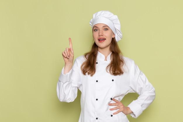 Vooraanzicht van vrouwelijke kok in wit kokkostuum dat haar vinger op groene muur opheft