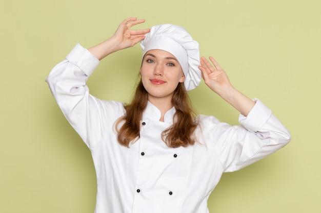 Vooraanzicht van vrouwelijke kok in wit kokkostuum dat op groene muur glimlacht