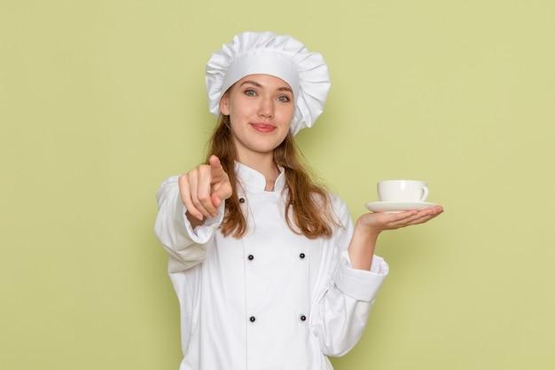 Vooraanzicht van vrouwelijke kok in wit kokkostuum die kop van koffie houden en op de groene muur glimlachen