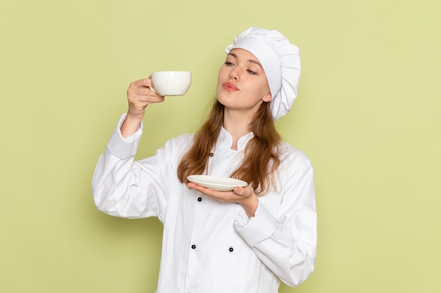 Vooraanzicht van vrouwelijke kok in wit kokkostuum die kop van koffie op de groene muur houden