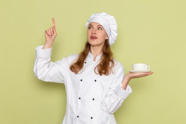 Vooraanzicht van vrouwelijke kok in wit kokkostuum die kop van koffie op lichtgroene muur houden