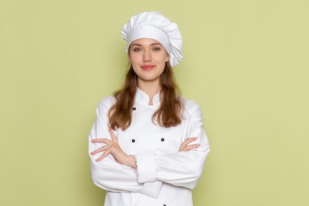 Vooraanzicht van vrouwelijke kok in wit kokkostuum het glimlachen stellen op groene muur
