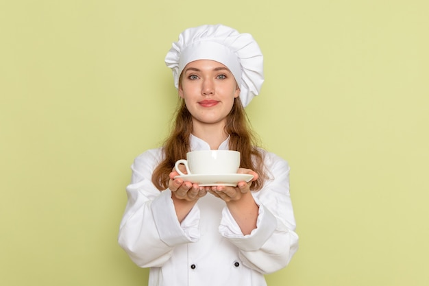 Vooraanzicht van vrouwelijke kok in witte kokkostuum die koffie op groene muur houden