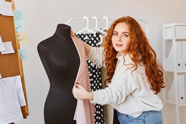 Vooraanzicht van vrouwelijke modeontwerper werken in atelier met jurk formulier