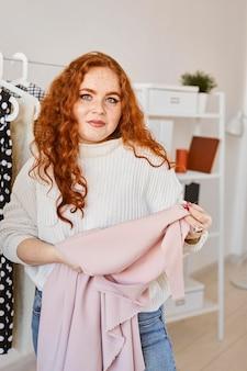 Vooraanzicht van vrouwelijke modeontwerper werken in atelier