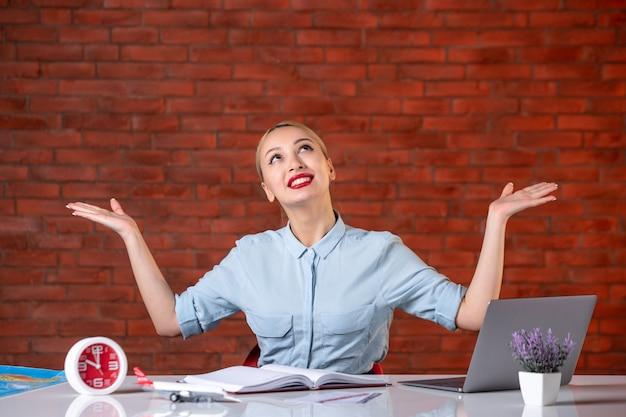 Vooraanzicht van vrouwelijke reisagent die achter haar werkplek zit toeristische bezetting wereldwijde service kaartservice binnenshuis assistent agentschap manager