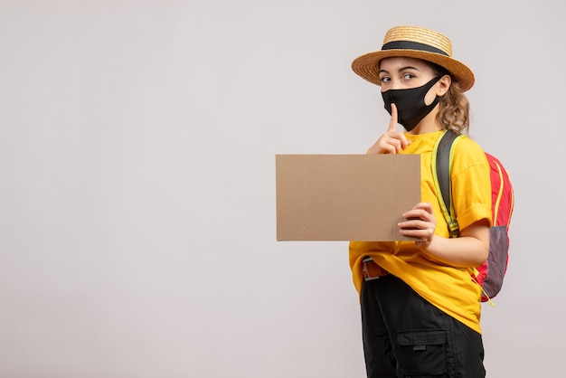 Vooraanzicht van vrouwelijke reiziger die met het karton van de rugzakholding hush-teken op grijze muur maken