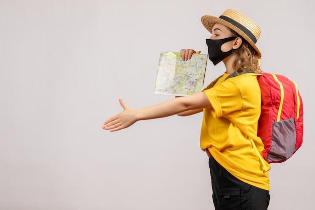 Vooraanzicht van vrouwelijke reiziger met de zwarte kaart die van de maskerholding hand op witte muur geeft