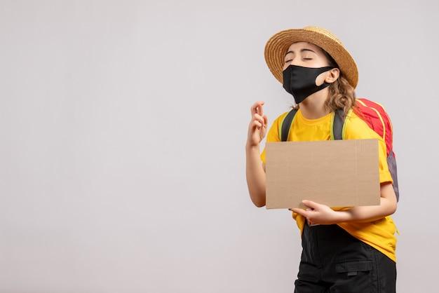 Vooraanzicht van vrouwelijke reiziger met het karton dat van de rugzakholding goed geluksteken op grijze muur maakt