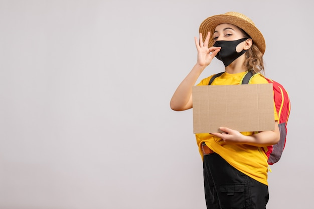 Vooraanzicht van vrouwelijke reiziger met het karton dat van de rugzakholding smakelijk teken op grijze muur maakt