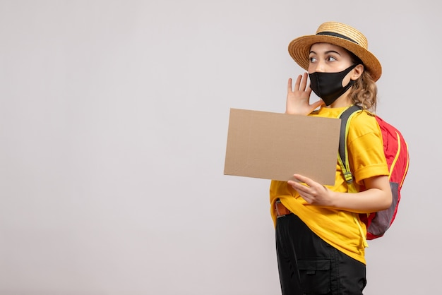 Vooraanzicht van vrouwelijke reiziger met het karton van de rugzakholding op grijze muur